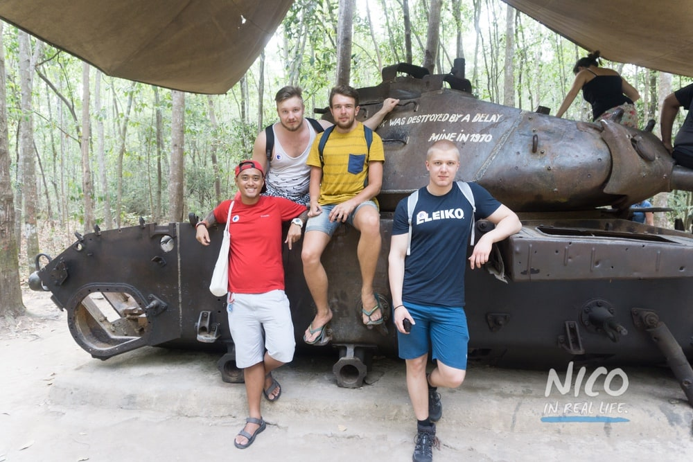 Standing by the tank with friends at the Cu Chi Tunnels in Vietnam